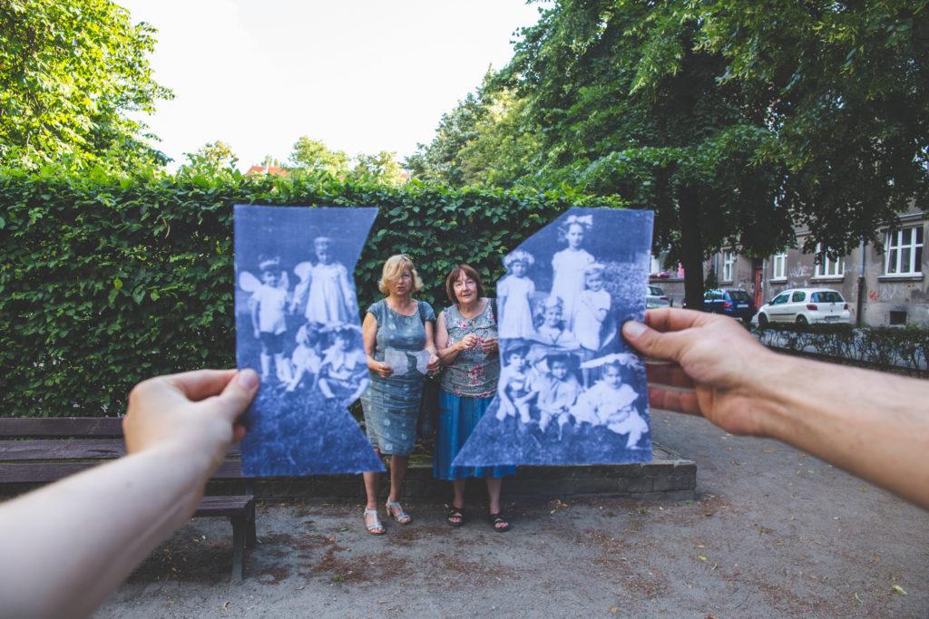Poziome zdjęcie: dwie kobiety w średnim wieku stoją przy żywopłocie na wrocławskim podwórku. Zza aparatu wystają dwie ręce, trzymające rozdartą archiwalną fotografię. Jedna z połówek znajduje się po lewej, a druga po prawej stronie pozujących pań.