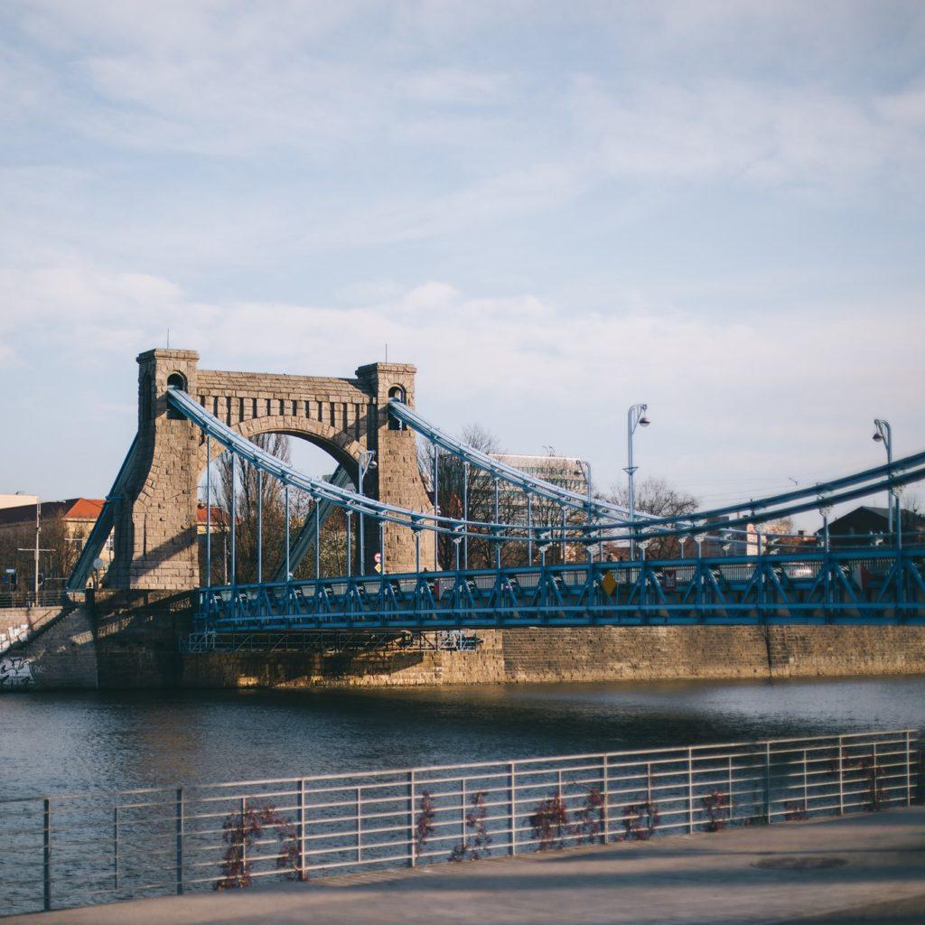 Zdjęcie przedstawia Most Grunwaldzki We Wrocławiu w jasny, słoneczny dzień.