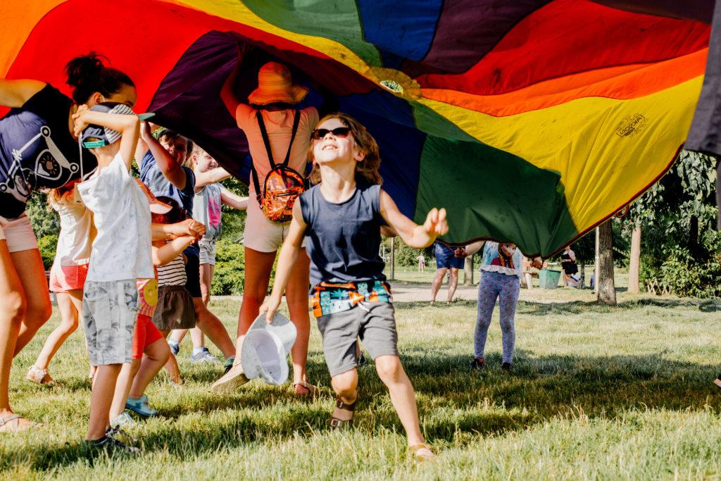 Słoneczny dzień. Grupa dzieci i animatorek bawi się pod kolorową chustą animacyjną. Na środku szeroko uśmiechnięty chłopiec w okularach przeciwsłonecznych.