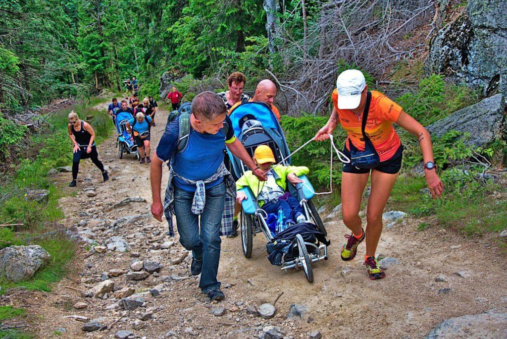 Stroma górska ścieżka. W tle gęsty las. Grupa ludzi wspina się na szczyt. Na pierwszym planie młoda kobieta w pomarańczowej koszulce oraz mężczyzna w niebieskiej koszulce ciągną na sznurkach sportowy wózek, w którym siedzi młody chłopak. Jednocześnie mężczyzna w pomarańczowej koszulce asekuruje wózek z tyłu oraz pcha go pod górę.