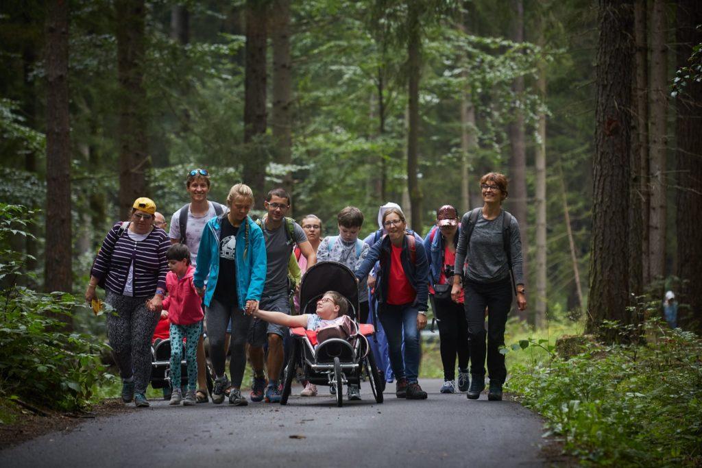 Grupa uśmiechniętych i szczęśliwych ludzi idzie ścieżką przez las. To uczestnicy i uczestniczki projektu Łączą nas góry. W samum środku grupy jedzie młoda dziewczyna na wózku. Trzyma za rękę i uśmiecha się do idącej obok Karoliny - wolontariuszki.