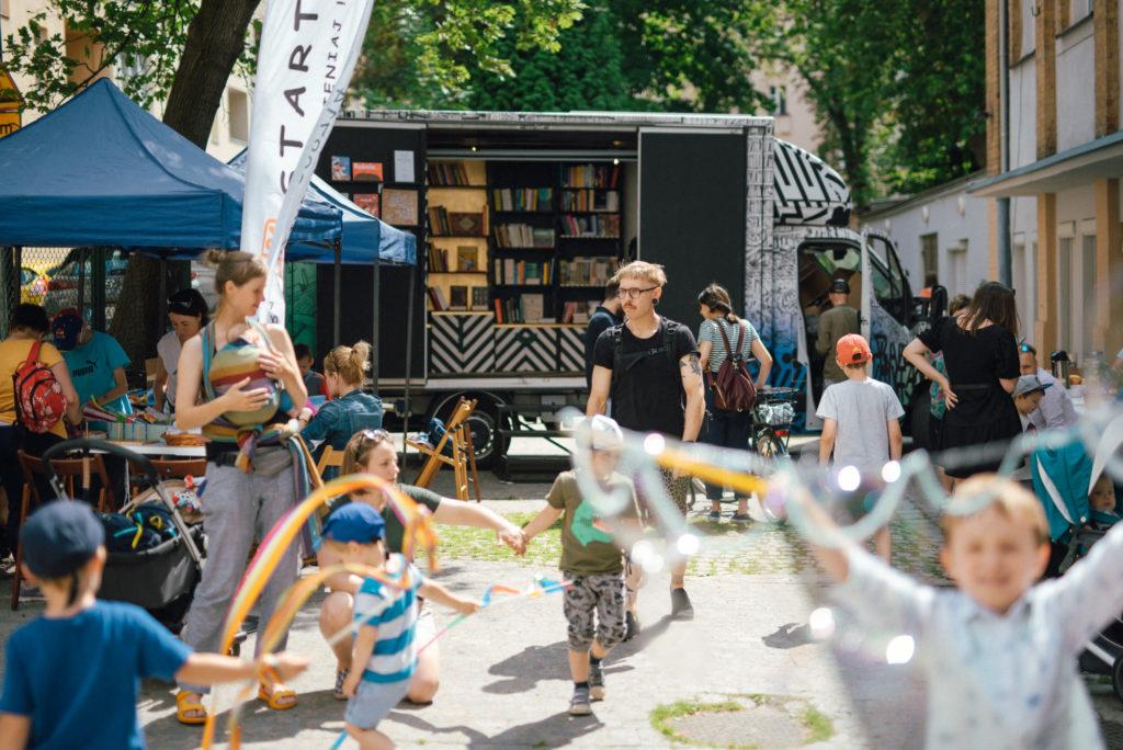 Grunwaldzki piknik sąsiedzki: w dolnej części zdjęcia gromadka dzieci puszczających bańki mydlane oraz bawiące się szarfami. Za nimi widoczne stoisko, przy którym osoby robią latawce. W tle busik z otwartym bokiem i książkami w środku - to mobilna księgarnia Tajnych Kompletów.