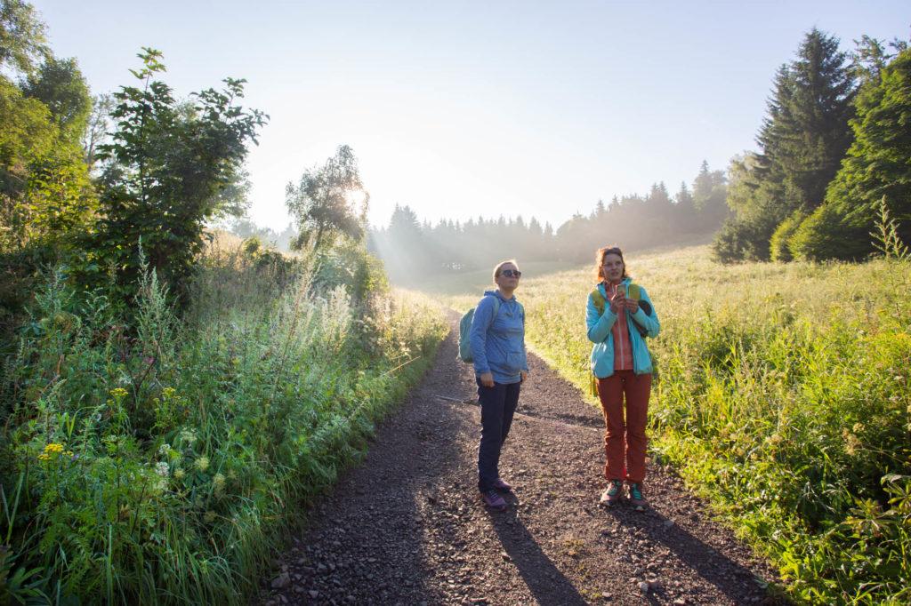 Dwie młode kobiety stoją na szerokiej ścieżce. Po obu stronach otacza je gęsta roślinność, wysokie trawy i krzewy. Za nimi wschodzące słońce rozświetla krajobraz.