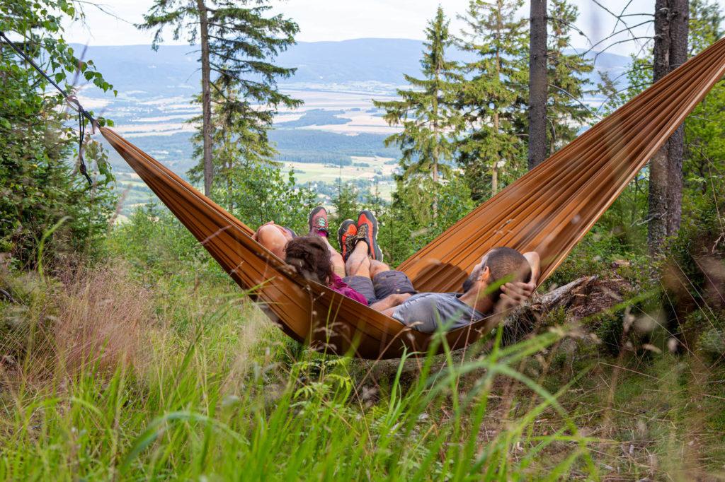 Hamak rozpięty miedzy drzewami, w hamaku dwie młode osoby. Rozmarzone patrzą na górski krajobraz widoczny przed nimi.