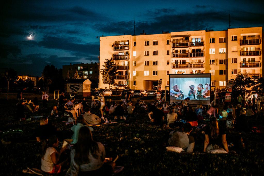 Noc, księżyc delikatnie świeci spomiędzy chmur. Na łące obok niskich bloków mieszkalnych rozstawiony jest duży ekran, a przed nim, na kocach siedzi duża grupa ludzi, oglądających film.
