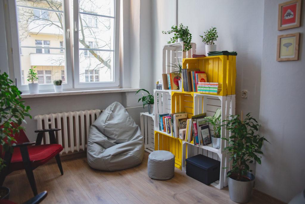 Jasne wnętrze pracowni komfortu. Pod Dużym oknem leży szary fotel-worek, oboek wypełniony książkami żółty regał.