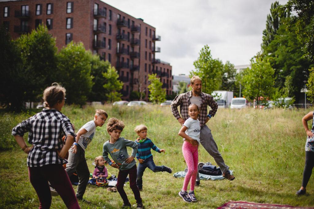 Grupa dzieci wraz z dwójką dorosłych tańczy na trawie między niskimi budynkami.